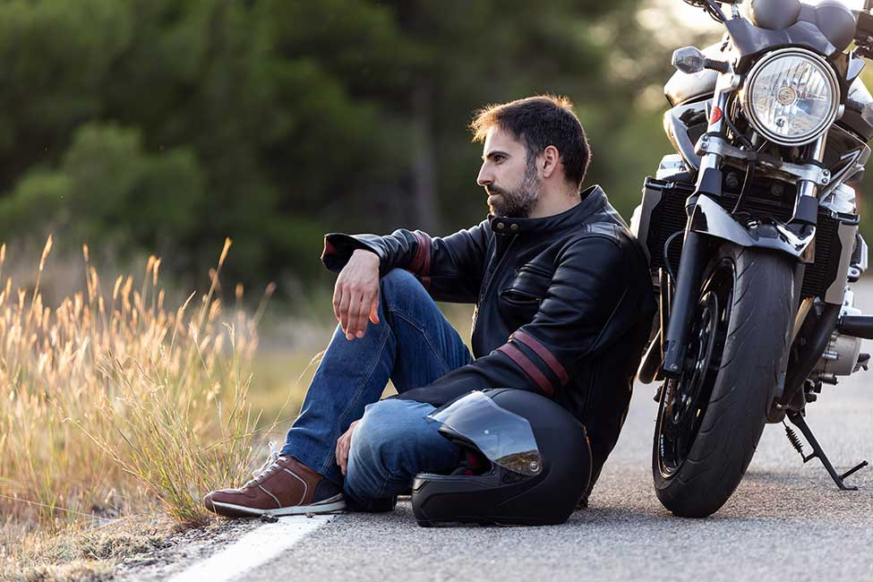 man sitting next to broken down motorcycle