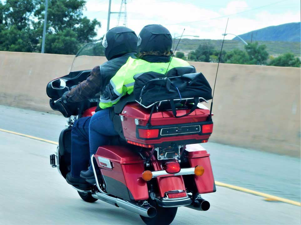 couple riding their honda motorcycle with a windshield